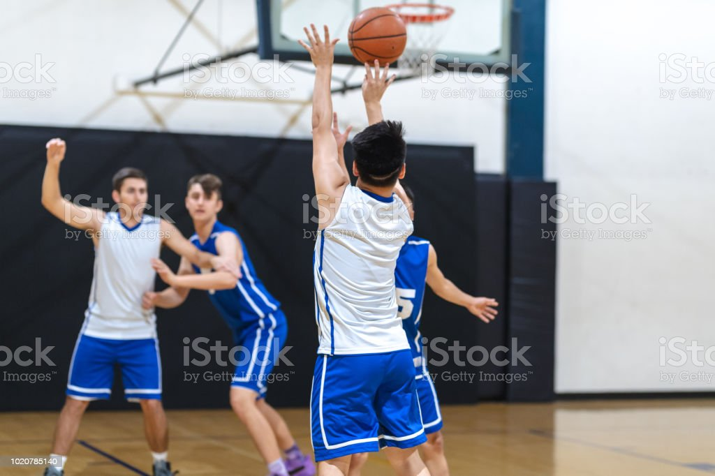 A high school player shoots a three pointer during a scrimmage as a...