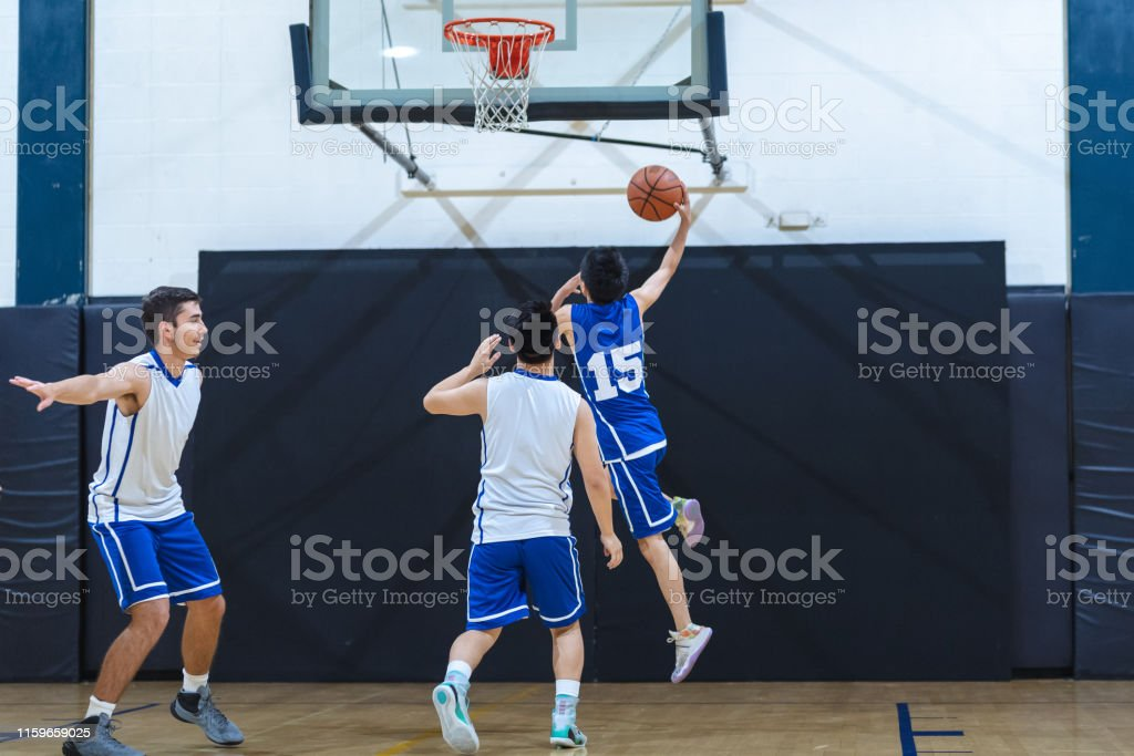 A high school player soars for a layup during a scrimmage as a...