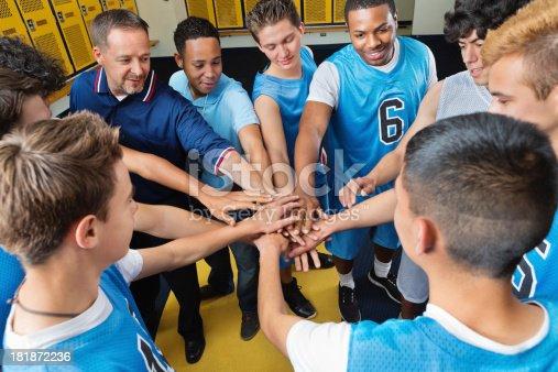 High school basketball team huddled in locker room before game