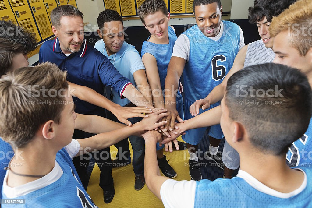 High school basketball team huddled in locker room before game stock photo