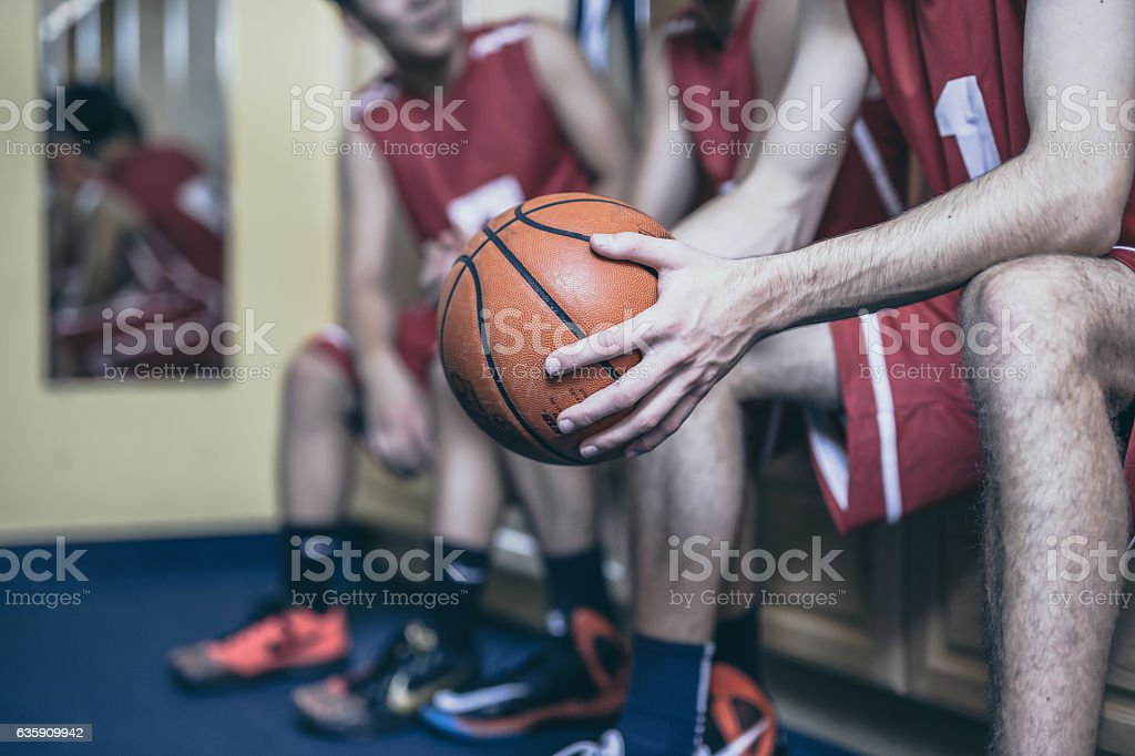 High school basketball teammates sitting together before a game stock photo