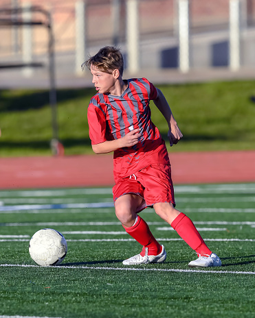 Young high school soccer player playing soccer. Very athletic young man displaying amazing soccer skills