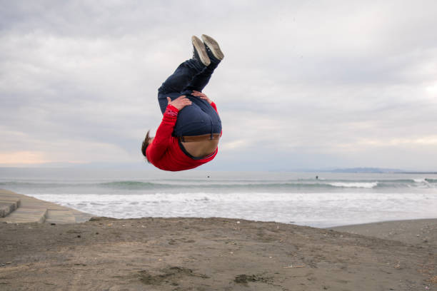 High school boy backflipping on beach stock photo