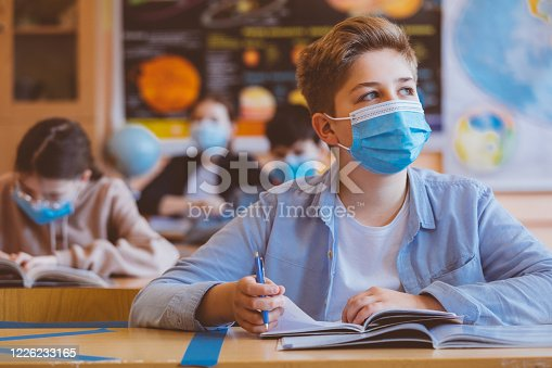 High school students at school, wearing N95 Face masks. Teenage boy sitting at the school desk, looking away and thinking.