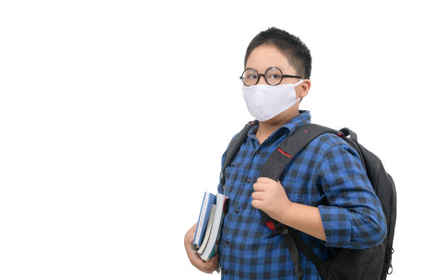A high school boy student wear mask and eye glasses carrying schoolbag isolated stock photo
