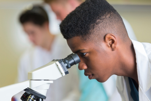 High school boy using microscope during science class