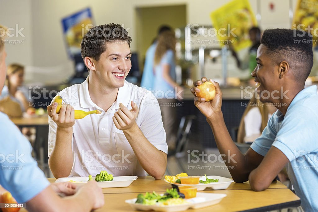 High school boys laughing together while eating lunch in cafeteria stock photo