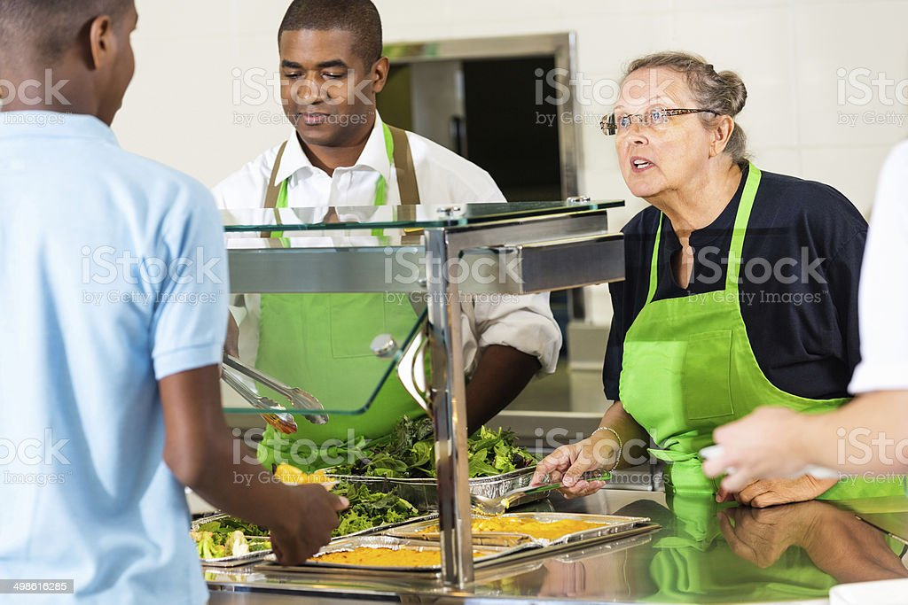 High school cafeteria lunchroom workers serving hot meal to students stock photo
