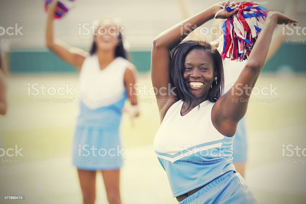 High school cheerleader performing routine at football game stock photo