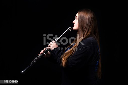 A teenage girl playing her clarinet for the High School band.