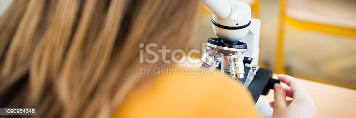 1097006206 istock photo High School female student in biology class. Student using microscope to examine samples. 1090954348