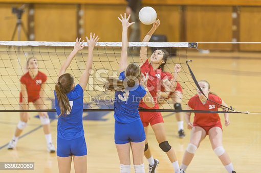 istock High school female volleyball player spiking the ball 639020060