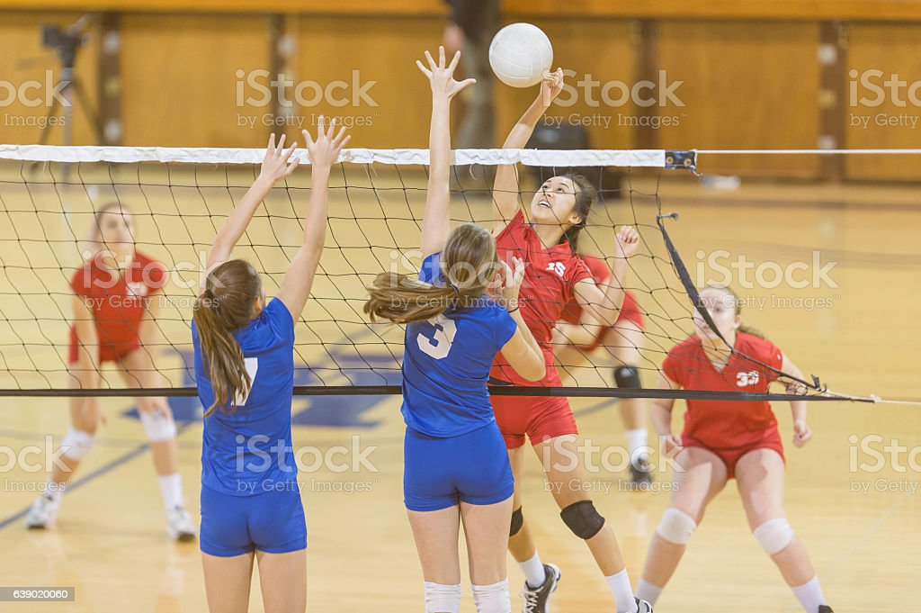 High school female volleyball player spiking the ball stock photo