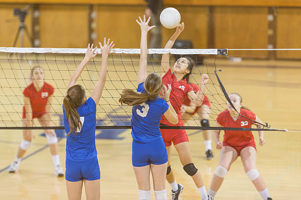 high school female volleyball player spiking the ball - volleyball sport stock photos and pictures