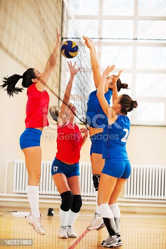 istock High school female volleyball team in action. 162321863