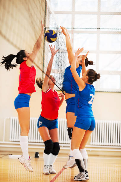 high school female volleyball team in action. - volleyball sport stock photos and pictures