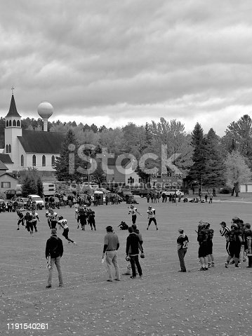 """High school football game in """"small town USA"""", done in black and white. It is a homecoming game with the photo taken of Unrecognizable coaches and and high school football students from a distance, they are camera unaware and making a play while running down the field. The photo looks and feels like a rural small town scene complete with church and water tower in the background."""