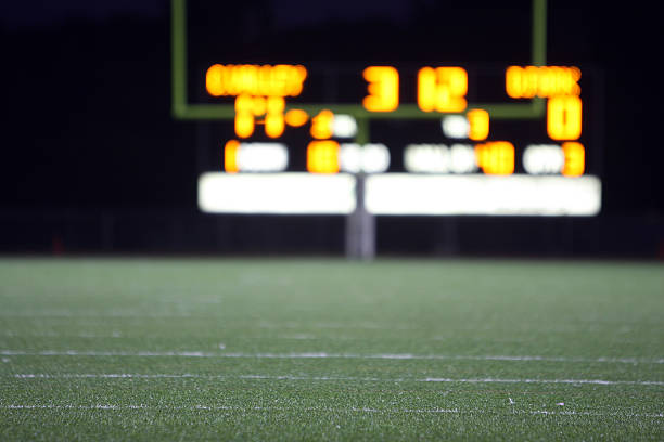 High school football score seen from distance Football field with defocused scoreboard in the background. scoring stock pictures, royalty-free photos & images