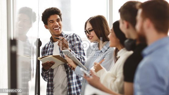 istock High school friends laughing, solving problems on whiteboard 1169954700