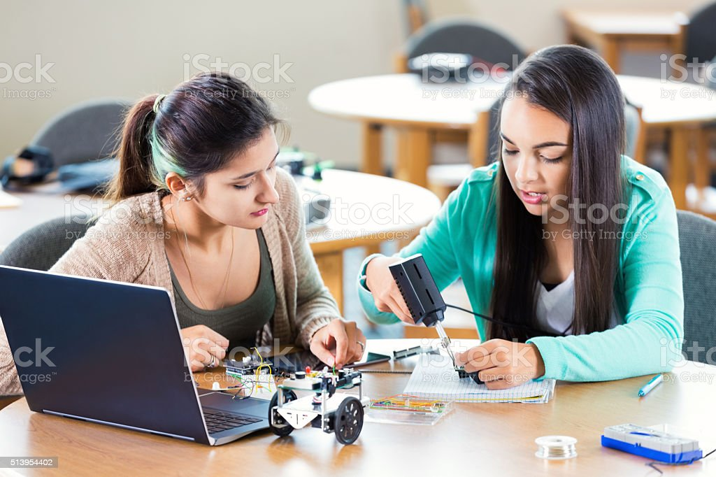 Two Hispanic female high school students are working on working on...