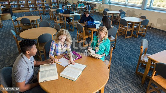 istock High school girl being tutored while mom waits in library 473745218