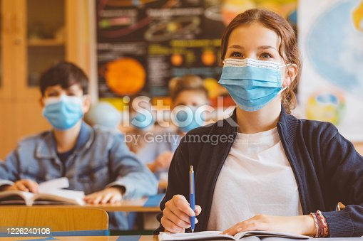 High school students at school, wearing N95 Face masks. Teenage girl sitting at the school desk and listening to the teacher.