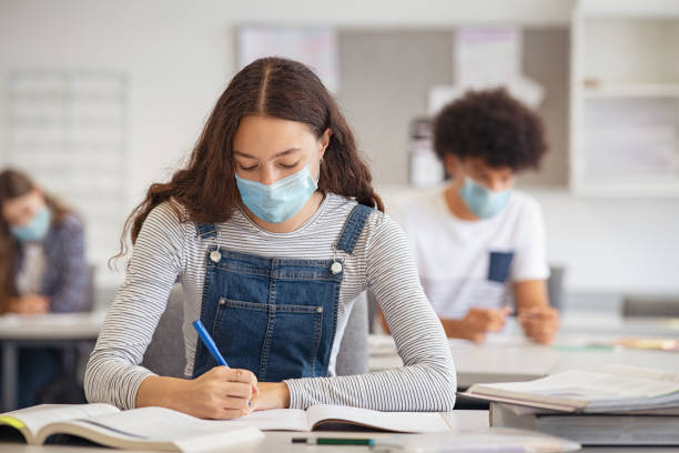 High school girl studying in class with face mask stock photo