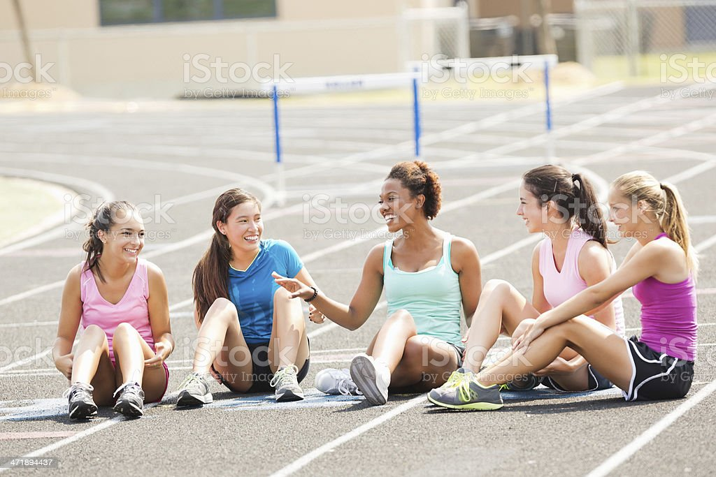 High school girls sitting on track laughing during gym class stock photo