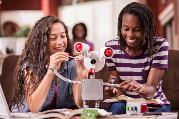 女子高校生は、教育、エンジニア リング科学のプロジェクトのためのロボットで動作します。 ストックフォト