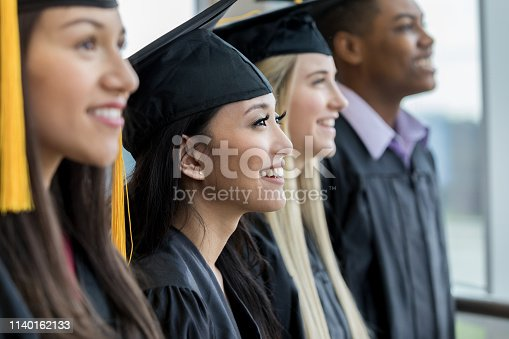 Divers group of high school of college graduates smiling during the graduation ceremony. They are standing in a row.