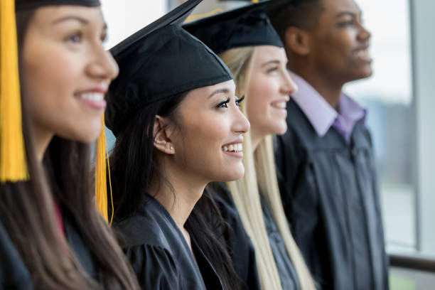 los graduados de secundaria en una fila - graduación fotografías e imágenes de stock