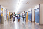A group of students walk down the hallway between periods. They are talking and smiling and carrying binders, backpacks, and books.