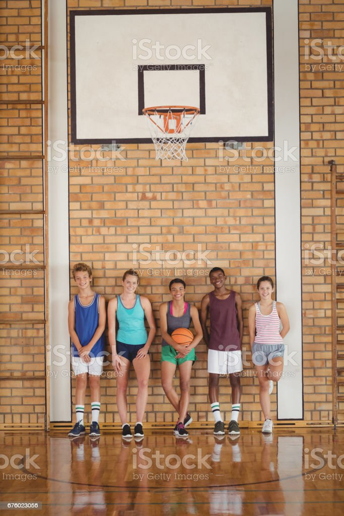 Portrait of high school kids leaning against the wall in basketball...