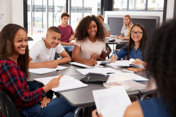 high school kids looking to teacher sitting at their desk - high school stock photos and pictures