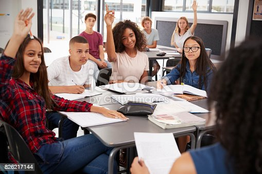 istock High school kids raise hands, teacher sitting at their desk 826217144