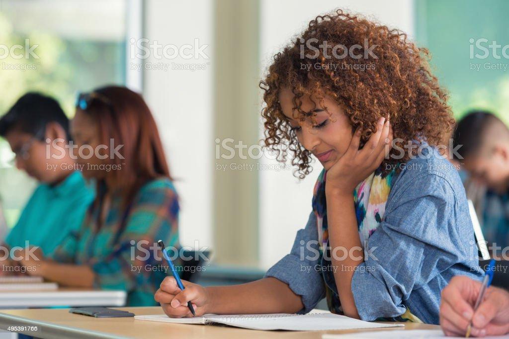 Escola ou fazendo exame menina da faculdade em sala de aula - foto de acervo