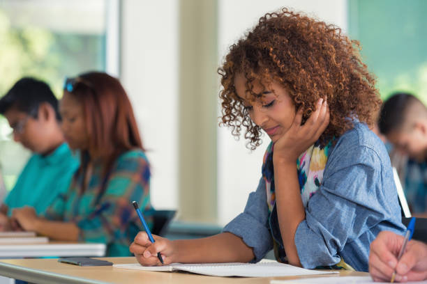 大学校または大学ガールてイグザムのスクール形式 - 作文の授業 ストックフォトと画像