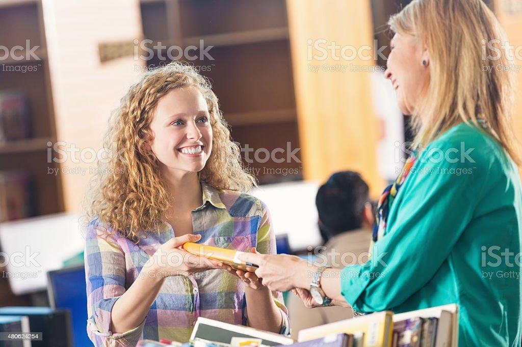 High school o college student comprobación de un libro en la biblioteca - foto de stock
