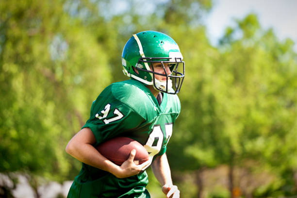 high school  or university american football player playing in field - high school sports stock pictures, royalty-free photos & images