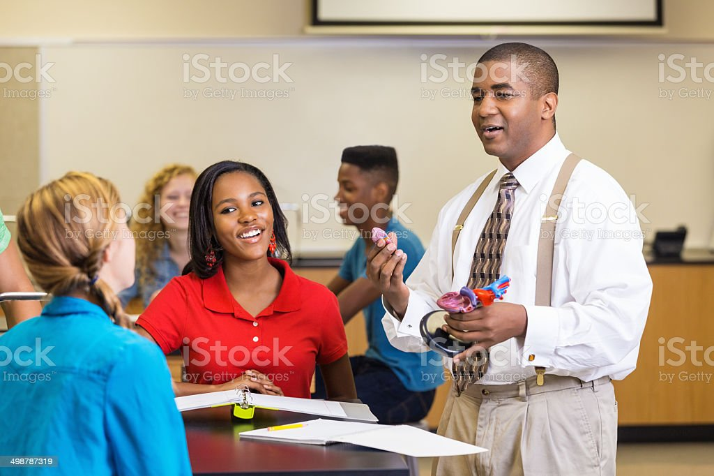 High School Science Teacher Explaining Heart Anatomy With Model ...