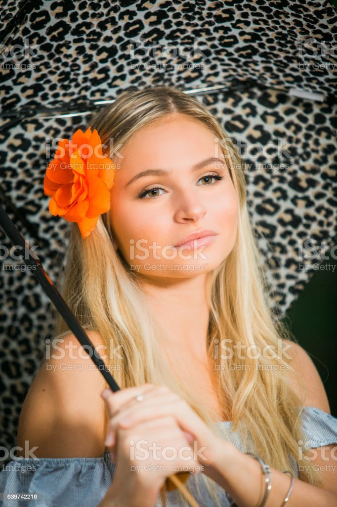 High school senior poses with umbrella for portraits rainy day stock photo