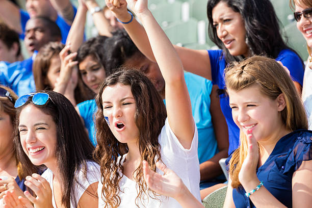 high school sports fans cheering for team in stadium - baseball sport stock photos and pictures