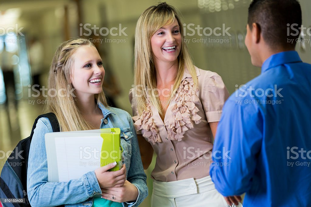 High school student and her mother talk with school principal stock photo