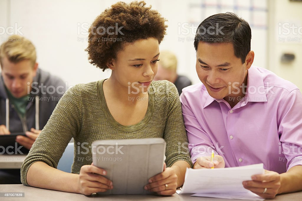High School Student And Teacher Using Digital Tablet stock photo