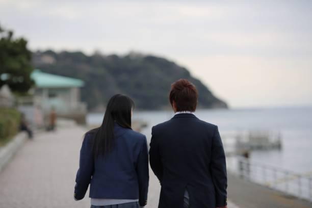 高中學生夫妻散步海灘邊圖像檔