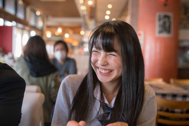 カフェで笑っている高校生女の子 ストックフォト
