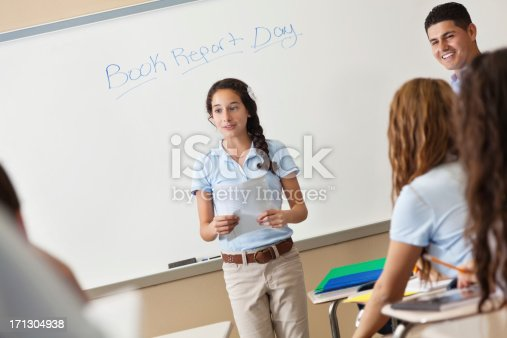 911029590 istock photo High school student giving book report presentation during class 171304938