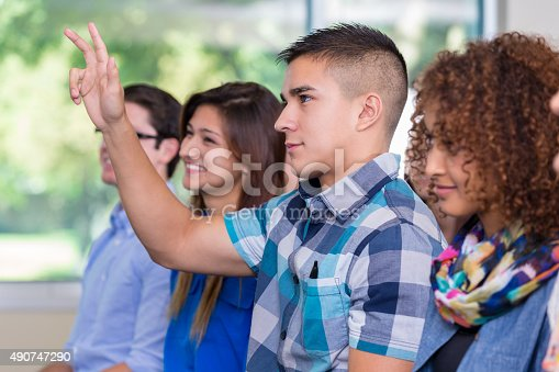 600055398 istock photo High school student raising hand during lecture or assembly 490747290
