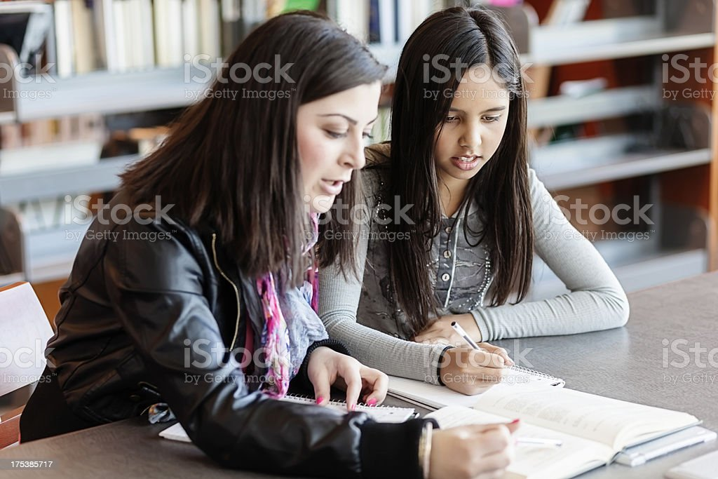 High School Student Tutors Elementary Age Girl in Library stock photo