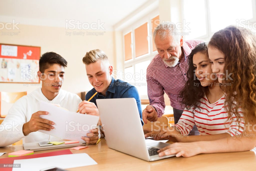 High school students and teacher with laptop. stock photo